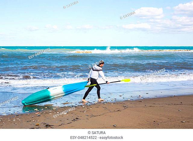Young man carrying his kayak along the shore