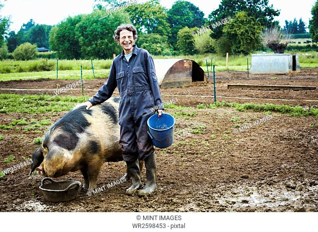 A woman stood by a large pig holding a bucket