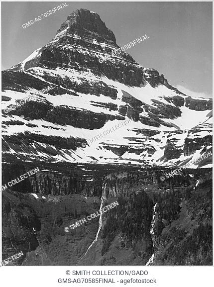 Black and white photograph, full view of snow covered mountain, including area below timberline, captioned 'In Glacier National Park', by Ansel Adams