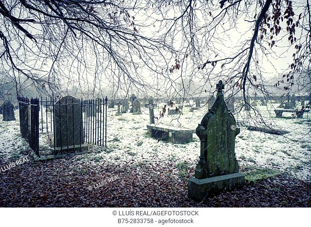 View of cemetery with graves, tombstones and trees in a snowy winter day. St Michael and All Angels Church, Linton, Grassington, Yorkshire Dales
