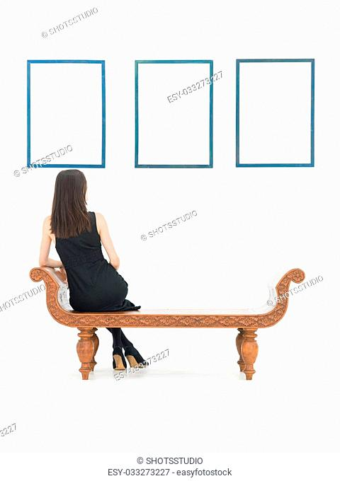 back view of woman sitting on a bench looking at empty frames displayed on white wall