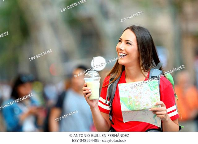 Happy teen tourist sightseeing holding a paper map in the street