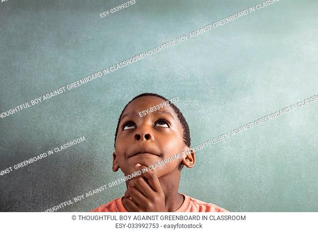 Thoughtful boy looking up against greenboard in classroom