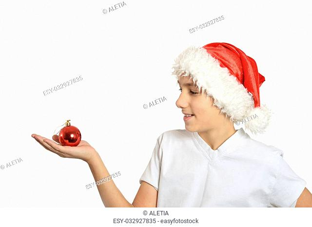 Boy in Santa hat with christmas ball on a white background