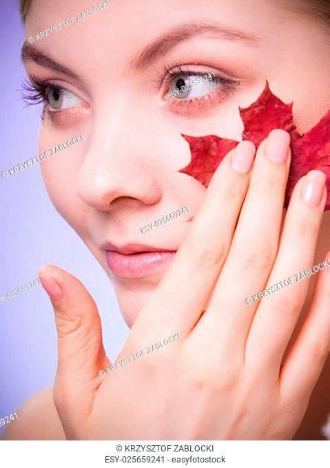 skincare habits. portrait of young woman with leaf as a symbol of red capillary skin on violet. face of a girl taking care of her dry complexion