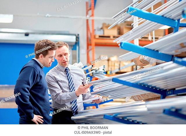 Manager and factory worker checking shelves of metal rods in roller blind factory