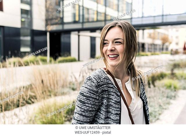Smiling young woman outside office building