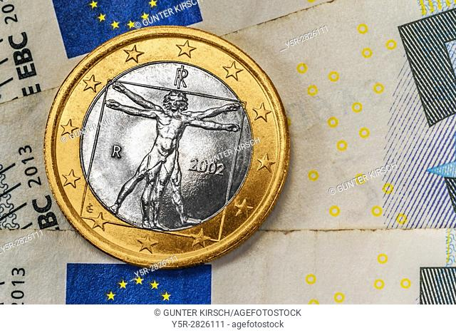 a 1 euro coin from Italy on euro banknotes