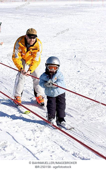 Boy 3 years is learning skiing with his father and is going by the ski lift MR