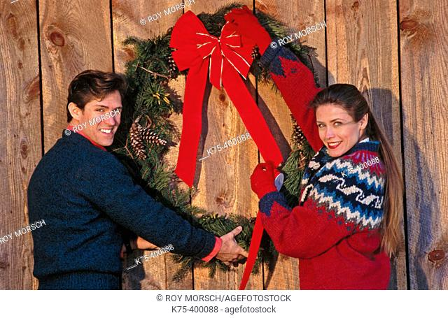 Couple putting up Christmas wreath