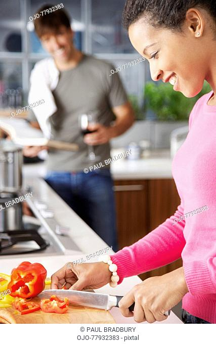 Woman cutting red peppers with man in background