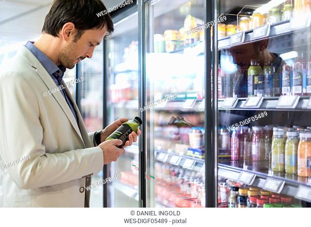 Mature man in supermarket choosing smoothie from cooling shelf