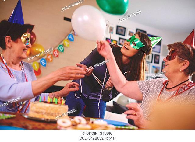 Senior women waving balloons at birthday party