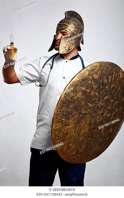 Shot of a male doctor in a helmet holding a shield and a syringe ready to vaccinate patients protective guardian healthcare soldier vitality safety prevention...