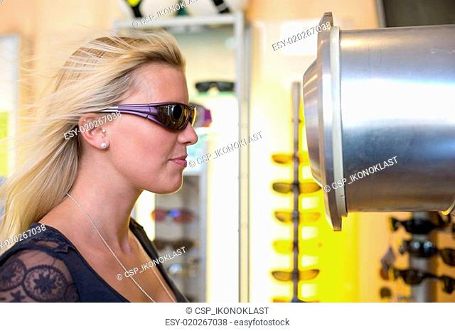 Customer testing whether sport eyeglasses are windproof in front of wind tunnel
