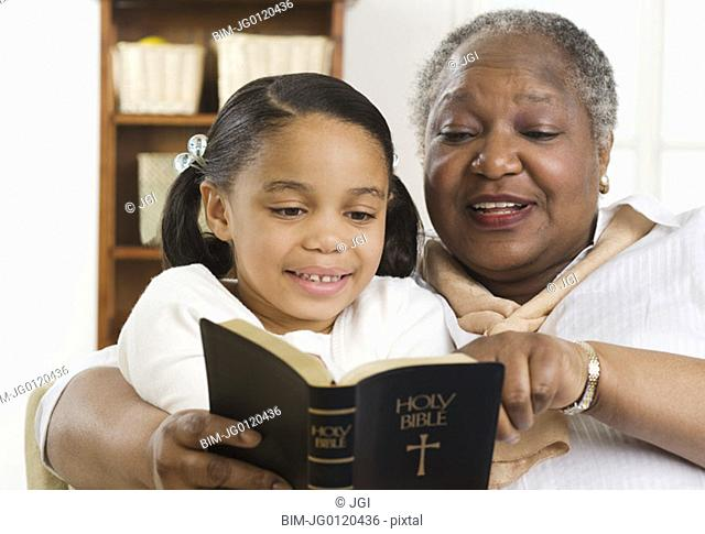 Senior woman reading the Bible to her granddaughter