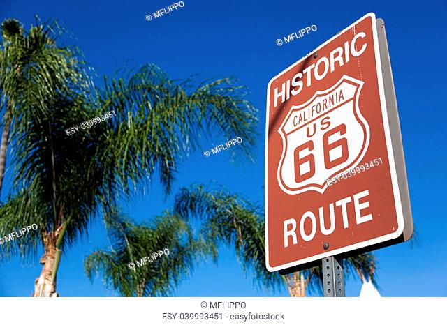 An historic route 66 highway sign with palm tree branches and a blue sky background
