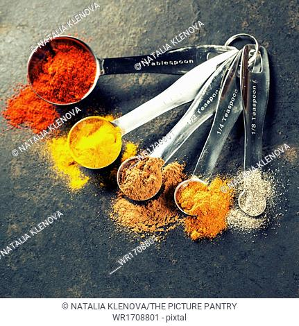 Colorful spices in metal spoons - beautiful kitchen image