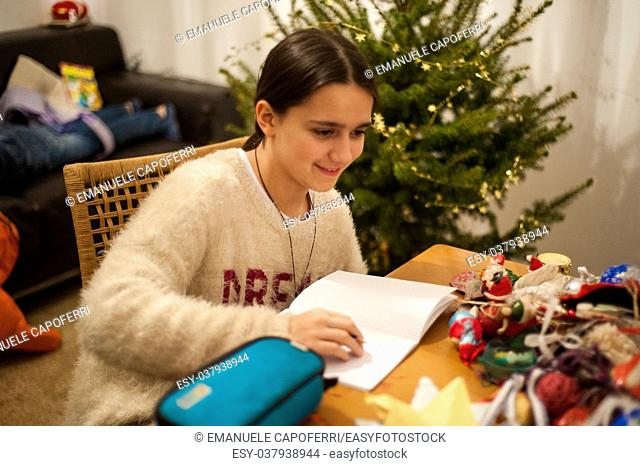 teenager does homework on the dining room table while smiling