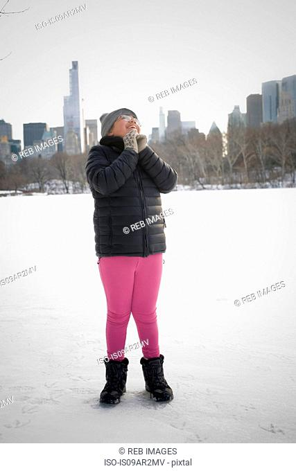 Young girl standing in snowy landscape, excited, New York, NY, USA