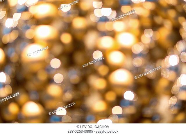 holidays, luxury and background concept - blurred golden christmas decoration or garland lights bokeh