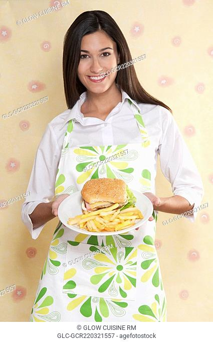 Portrait of a woman holding a plate of burger and fries