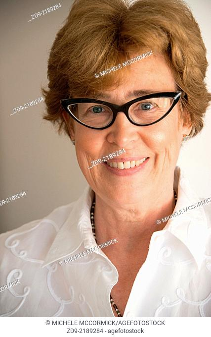 A middle aged woman smiles through her cat's-eye glasses