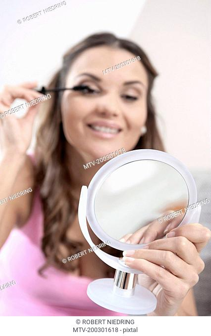 Young woman holding beauty mirror for applying mascara