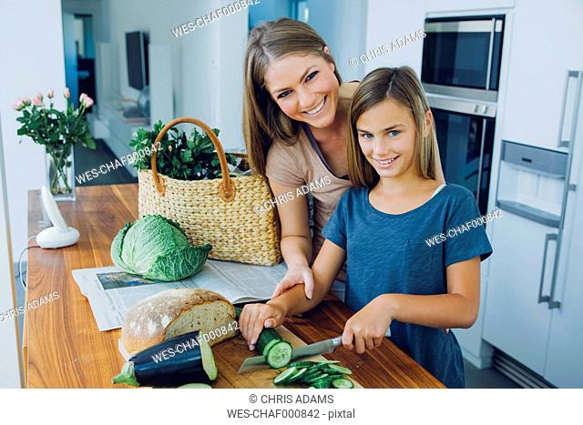 Mother and daughter in kitchen slicing cucumber