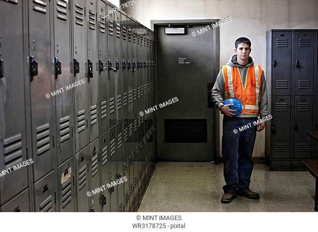 View of a young Caucasian factory worker wearing a safety vest and standing next to lockers in a factory break room