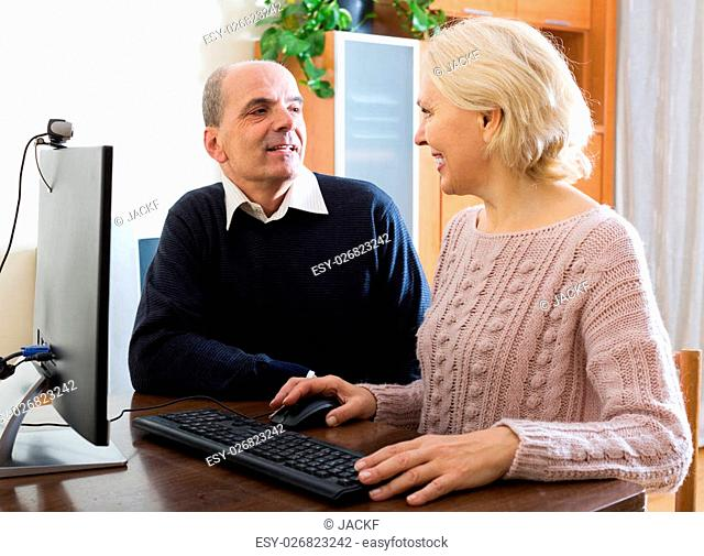 Happy pensioners are sitting in front of PC with headphones indoor