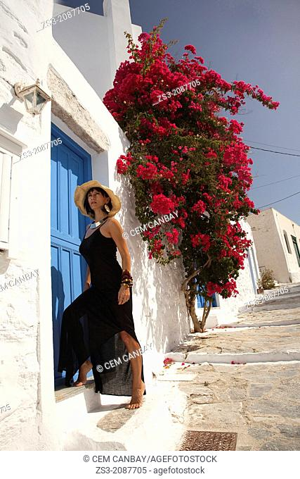 Woman posing in front of a house door, Amorgos, Cyclades Islands, Greek Islands, Greece, Europe
