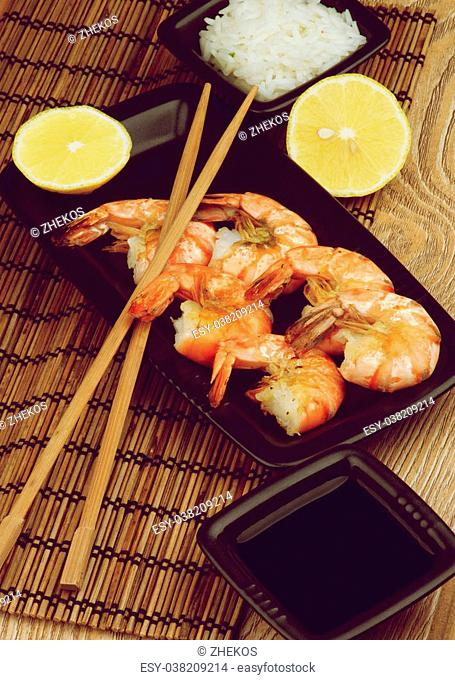 Delicious Roasted Shrimps with Soy Sauce, Boiled Rice, Lemons and Chopsticks in Asian Style closeup Straw Mat background