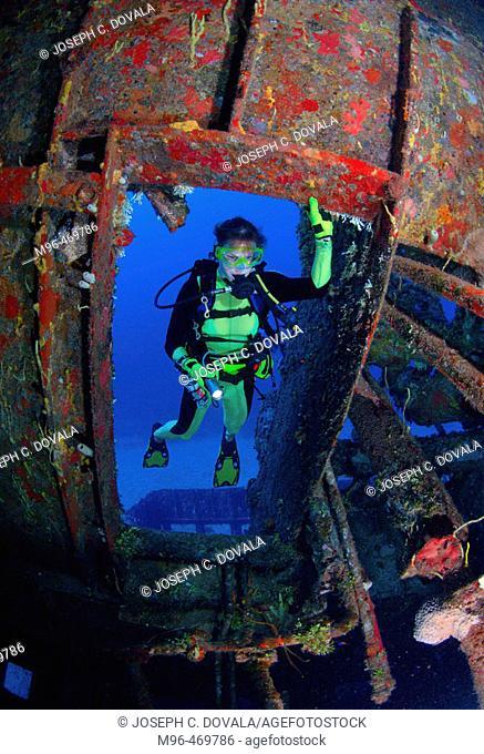 Female scuba diver entering shipwreck. Roatán, Honduras
