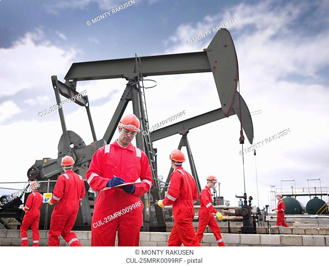Workers with oil well pumps