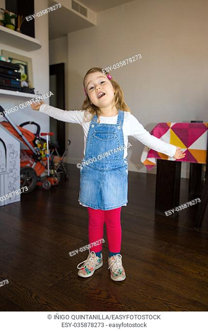 portrait of three years old blonde girl, with blue jeans dress, standing indoor house, singing with open arms looking