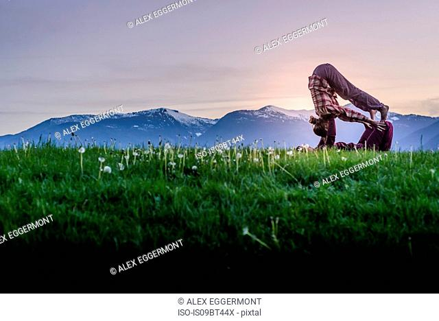Two young women practicing acroyoga on grass in front of mountain range at sunset, Squamish, British Columbia, Canada