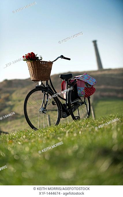 an old fashioned 'sit up and beg' bicycle with whicker basket outdoors in a field summer evening