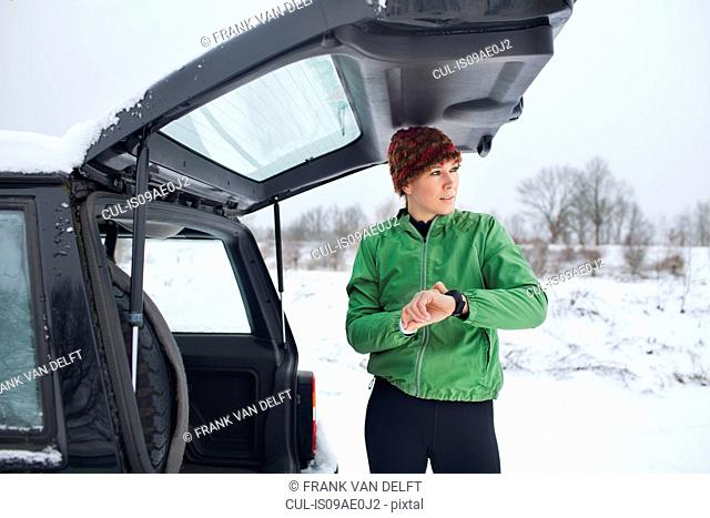 Female jogger preparing for run in snow covered scene