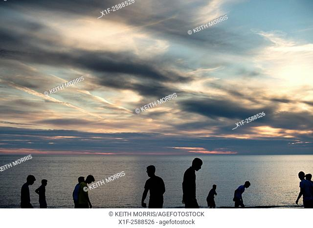 10 Boys young men in silhouette playing on a beach at dusk, UK