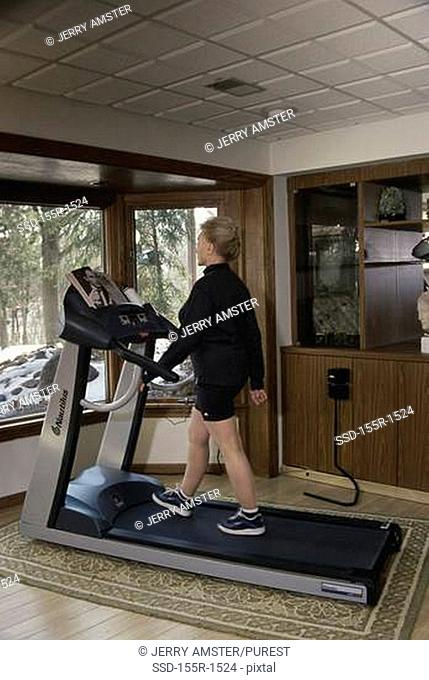 Side profile of a mid adult woman walking on a treadmill