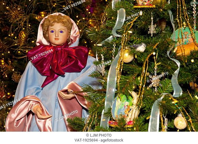 angel beside a decorated christmas tree, edmonton, alberta, canada