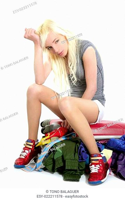 young fashion travel girl closing full clothes suitcase vacation