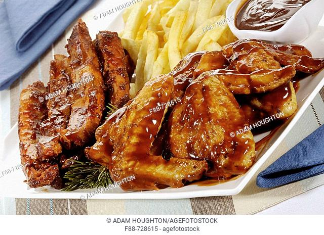 Meat platter with marinated chicken wings and ribs with sauce and chips, food