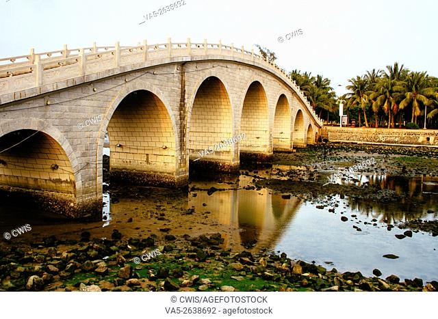 Haikou, Hainan Island, China - The view of a stone arch bridge at sunset