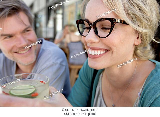Couple drinking cocktail at city sidewalk cafe