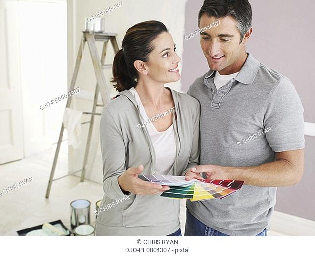 Man and woman looking at paint samples in room with ladder