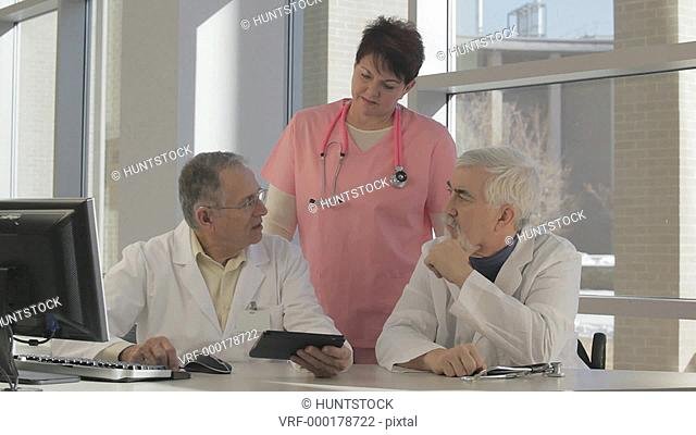 Two doctors and a nurse using a computer and tablet, one doctor with Muscular Dystrophy