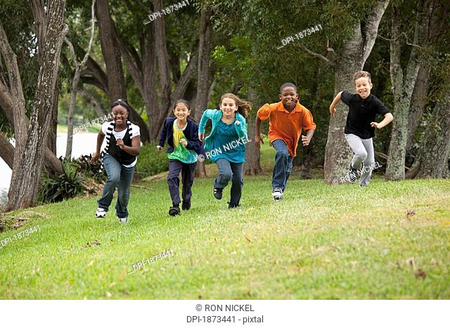 fort lauderdale, florida, united states of america, a group of preteesn running to race each other in the park