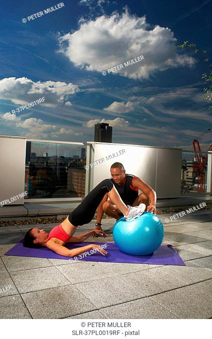Woman exercising with trainer on rooftop